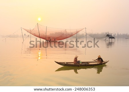 Unidentified people on boat in early morning on river in Hoian, Vietnam. Hoian is recognized as a World Heritage Site by UNESCO. - stock photo