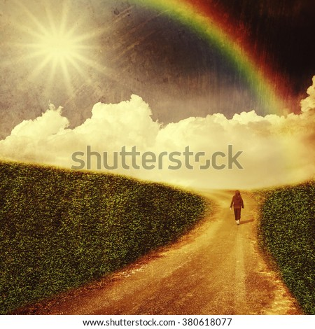 Unidentified people walking through the fields in country road with white cloud, sunbeam and rainbow. retro film filtered, instagram style - stock photo