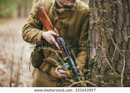 Unidentified re-enactor dressed as Russian Soviet soldier in camouflage in forest - stock photo