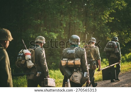 Unidentified re-enactors dressed as German soldiers during march through summer forest - stock photo