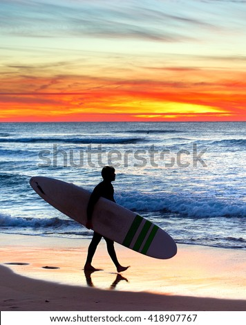 Unidentified surfer on the ocean beach at  sunset. Portugal - stock photo