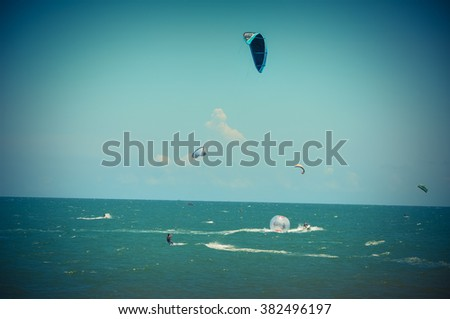 Unidentified surfers kite surfing and playing water sports at Phan Thiet beach, a tourist attraction for both tourists and local for beach resorts and recreation activities at central coast of Vietnam - stock photo