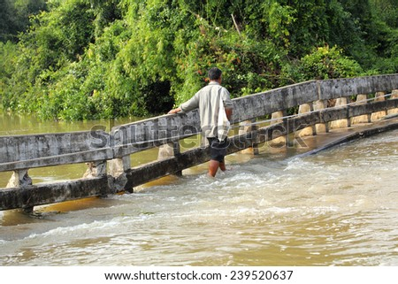 Unidentified Thai citizen walking by rope support across destroyed bridge after flooding at Mool river Thailand - stock photo