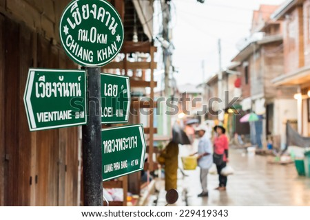 Unidentified tourists offering sticky rice to Buddhist monk and Buddhist novice in the morning at Chiang Khan, Loei, Thailand. - stock photo