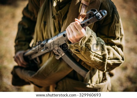 Unidentified woman re-enactor dressed as a Soviet military soldier with a submachine gun in hand. Close up on hands - stock photo