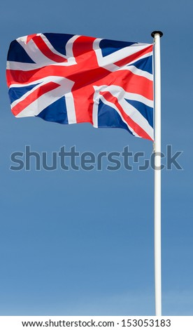 union jack british flag flying in a blue sky backdrop - stock photo