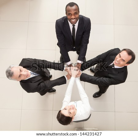 Union of successful businesspeople with hands on top of each other. Top View - stock photo