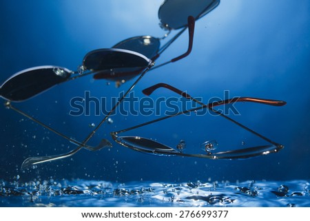 Unique abstract shot of sunglasses in water on gradient blue background  - stock photo
