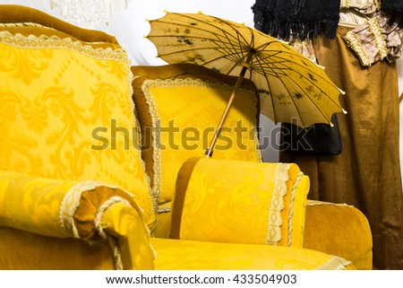 Unique background of old fashion arm chair with yellow upholstery and parasol placed beside it by vintage clothing hanging against wall - stock photo