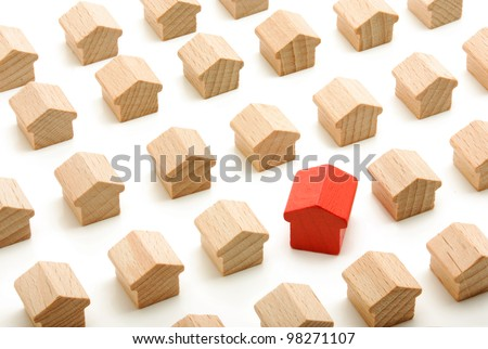 Unique house in group of wooden houses on white background - stock photo