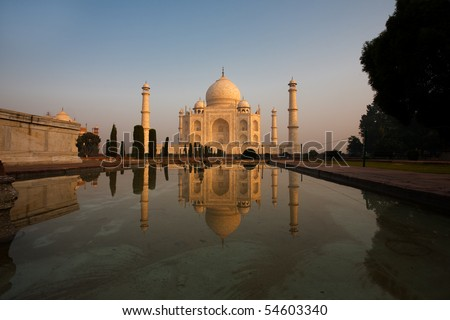 Unique image of front facade of Taj Mahal reflected in the side central water fountain while glowing with colorful morning sunrise red in Agra, India. Horizontal copy space - stock photo