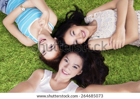 Unique perspective of teenage girls relaxing on grass while taking selfie with smartphone at field - stock photo