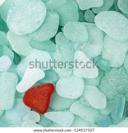 Unique red sea glass isolated on green sea glass background - stock photo