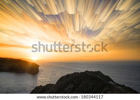 Unique time lapse stack sunrise landscape over rocky coastline - stock photo