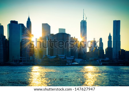Unique view of East River and New York City  skyline with sun reflecting off buildings of lower Manhattan at sunset. - stock photo