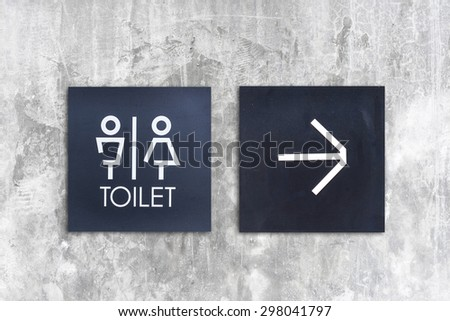 Unisex restroom or toilet and arrow sign on  concrete wall style boutique . - stock photo