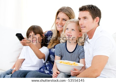 United family watching television together at home - stock photo
