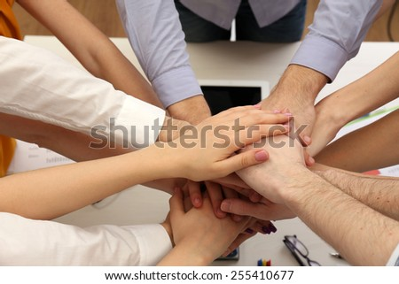 United hands of business team on workspace background top view - stock photo