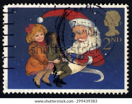 UNITED KINGDOM - CIRCA 1997: A stamp printed in the United Kingdom shows Children and Santa pulling a Christmas Cracker, circa 1997 - stock photo