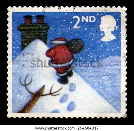 UNITED KINGDOM - CIRCA 2004: A used British postage stamp depicting a snowy scene of Santa Claus delivery presents at Christmas, circa 2004. - stock photo