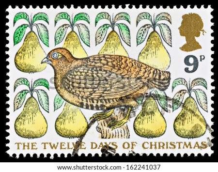 UNITED KINGDOM - CIRCA 1977: Used Christmas Postage Stamp depicting the Carol The Twelve Days of Christmas showing a Partridge in a Pear Tree, circa 1977 - stock photo