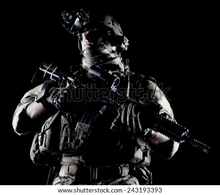 United States Army ranger with assault rifle on dark background - stock photo