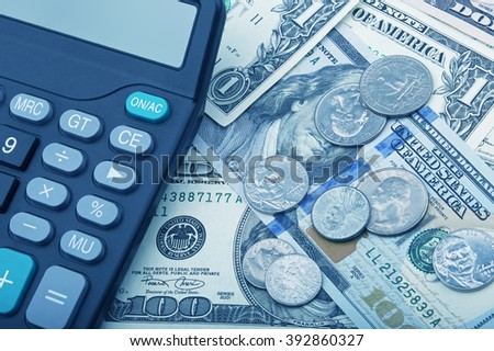 United States bank notes and coins with a calculator - stock photo