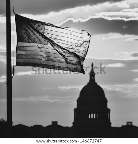 United States Capitol building and US flag silhouette at sunrise, Washington DC - Black and white toned  - stock photo