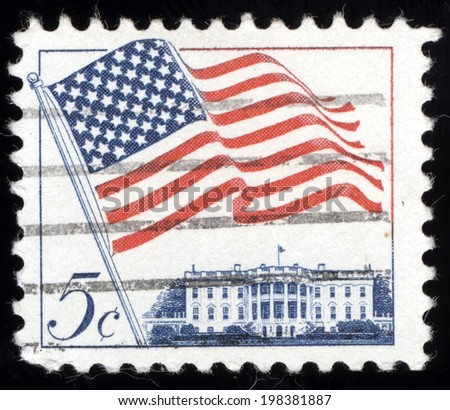 UNITED STATES - CIRCA 1962: A 5 cents stamp printed in the United States features waving US flag, circa 1962  - stock photo