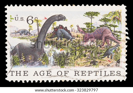 UNITED STATES OF AMERICA - CIRCA 1970: A postage stamp printed in United States shows a several dinosaurs and the text the age of reptiles. Centenary of American Natural History Museum, circa 1970 - stock photo