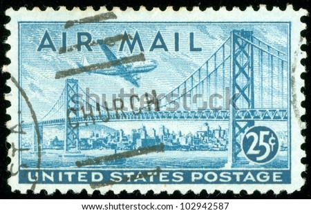 UNITED STATES OF AMERICA - CIRCA 1947: a stamp printed in the United States of America shows plane over San Francisco Oakland Bay Bridge, circa 1947 - stock photo