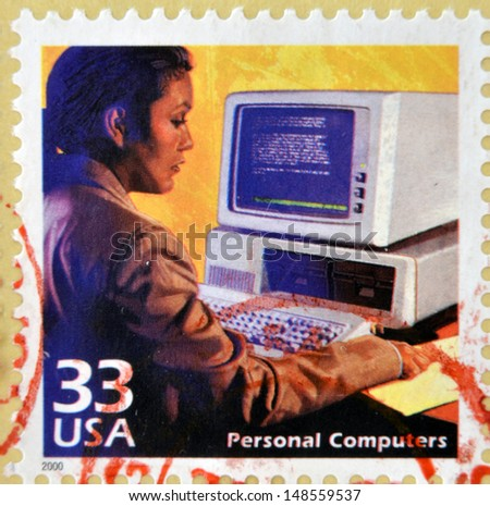 UNITED STATES OF AMERICA - CIRCA 2000: a stamp printed in USA showing an image of a woman using an old computer, circa 2000.  - stock photo