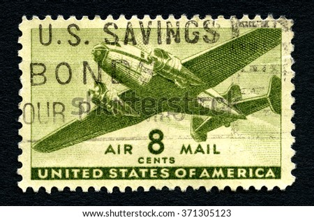 UNITED STATES OF AMERICA - CIRCA 1944: A used Air Mail postage stamp from the United States of America, picturing a transport aircraft, circa 1944. - stock photo