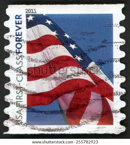 UNITED STATES OF AMERICA - CIRCA 2011: first class forever stamp printed in USA shows flying American flag against blue sky, six wavy stripes & five pointed stars; red blue; Scott 4519; circa 2011 - stock photo