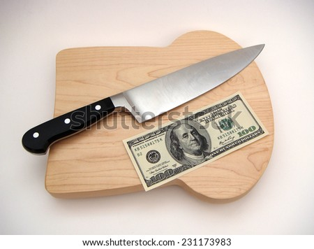 United States One Hundred Dollar Federal Reserve Note Resting Alongside A Chef's Knife On A Bread Shaped Cutting Board Over White Surface With Slight Vignetting. - stock photo