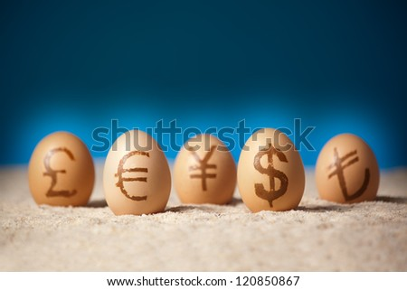 Universal currency units painted on eggs on the sand - stock photo