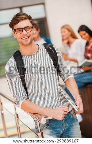 University life is great! Smiling young man holding laptop and looking at camera while his friends standing in the background - stock photo