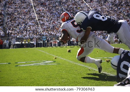 UNIVERSITY PARK, PA - OCT 9: Illinois running back No. 5  Mikel Leshoure is tackled after a long gain during a game against Penn State at Beaver Stadium on October 9, 2010 in University Park, PA - stock photo
