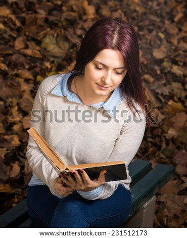 University redhead girl sitting in park and reading a book - stock photo
