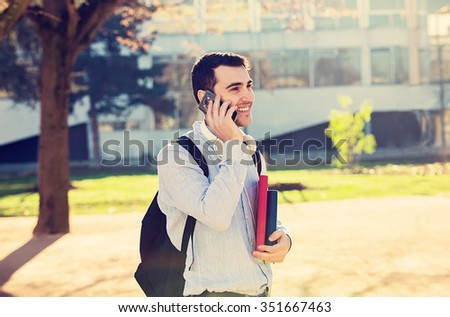 University.Smiling young student man talking on phone mobile holding a book and a bag on a university background .Young smiling student  outdoors Life style.City.Student. - stock photo