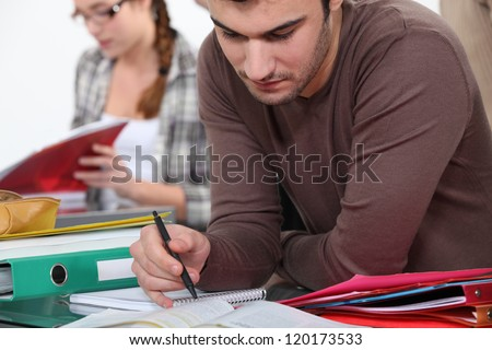 University student completing assigned reading - stock photo