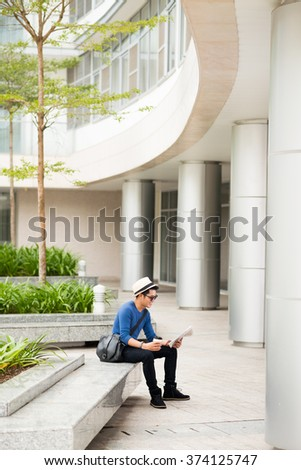 University student reading newspaper on campus - stock photo