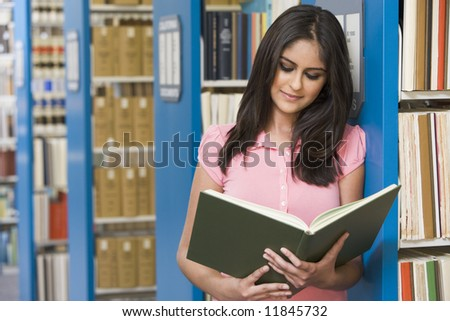 University student studying book in library - stock photo