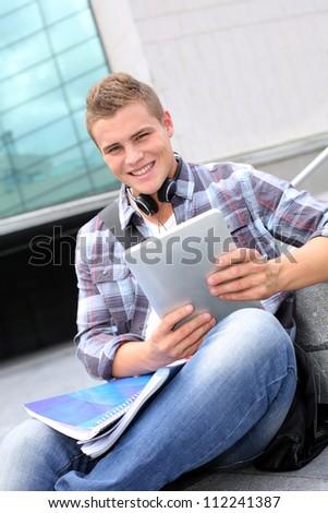 University student using digital tablet and headphones - stock photo
