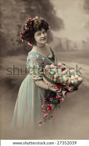 UNKNOWN - CIRCA 1915: An unidentified woman holds a basket of colored Easter egg in this Victorian Era hand-tinted portrait circa 1915 taken in an unknown location. - stock photo