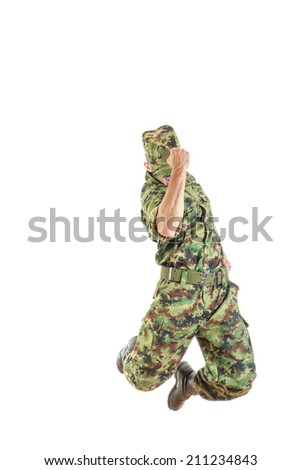 unknown soldier with hidden face in green camouflage uniform and hat jumping up in air with fist sign of success - stock photo
