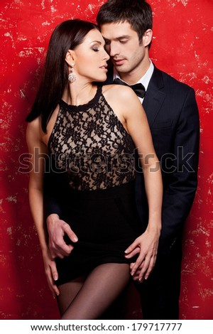 Unleashed desire. Beautiful young well-dressed couple bonding while standing against red background  - stock photo