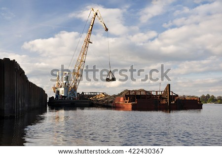 Unloading the barge with river sand at the pier.