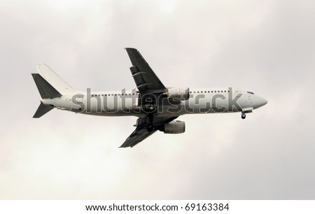 Unmarked white jet airplane in leveled  flight - stock photo