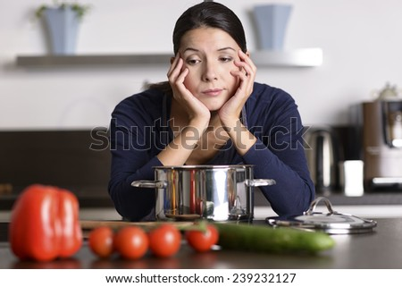 Unmotivated attractive young woman preparing the dinner leaning on the hob eyeing the fresh vegetables with a listless glum expression as she stands in her kitchen in an apron - stock photo